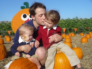 father and sons at a pumpkin patch